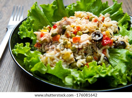 tuna salad with rice and vegetables on black dish  - stock photo