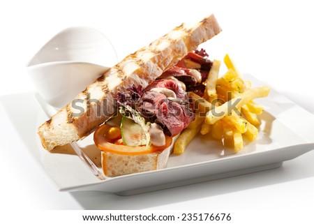 Tuna Sandwich Garnished with Fries and Sauce - stock photo