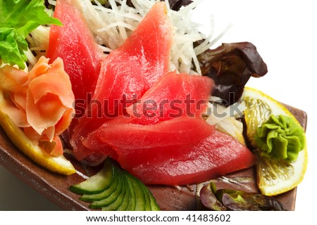 Tuna Sashimi - Maguro (fresh raw tuna) on Daikon (White Radish). Garnished with Ginger, Wasabi, Seaweed, Cucumber, Salad Leaf and Lemon - stock photo