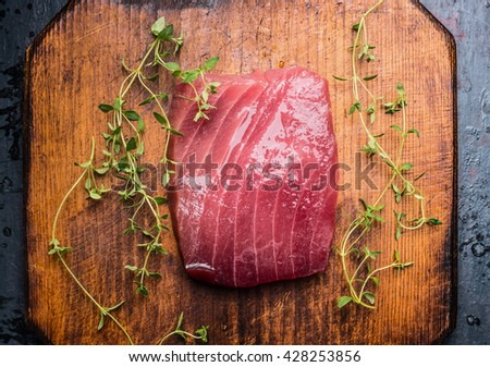 Tuna steak on rustic wooden background with fresh herbs, top view, close up. Seafood concept - stock photo