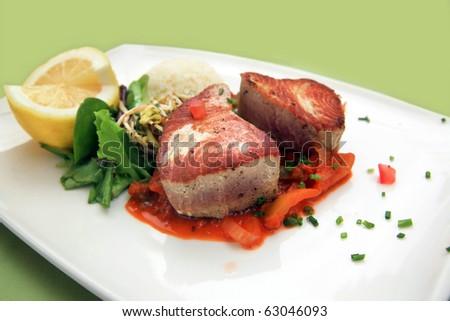Tuna steak: Oven grilled tuna steak served over orange pepper ratatouille, rice, salad and half lemon. - stock photo