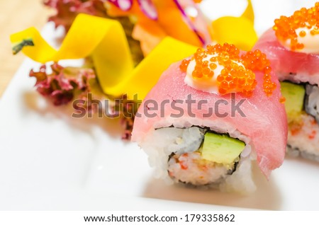 Tuna sushi with avocado inside on white dish - stock photo
