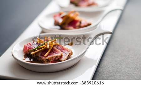 Tuna Tataki is a Japanese dish which consist of briefly seared tuna steak in thin slices. Served as appetizer with brandy sauce and garnish on a dark background. - stock photo