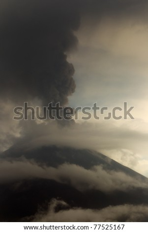 Tungurahua volcano eruption, May 2011. Large qty of ash darkning the sky.Vertical composition. - stock photo