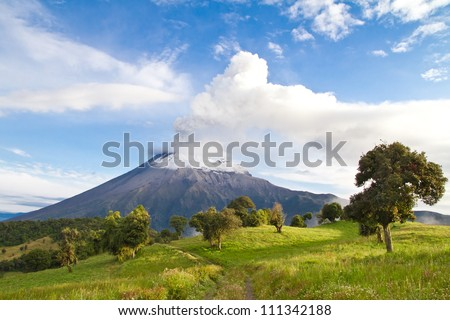 Tungurahua Volcano landscape, erupting at sunrise throwing smoke and ashes
