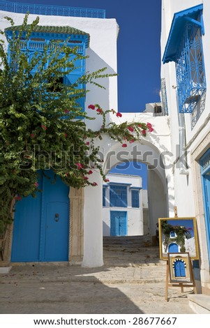 Tunisia. Sidi Bou Said - typical building with white walls, blue doors and windows. Framed pictures (on easel) are taken by me - stock photo