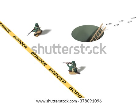 Tunnel and Set of Footprints From Unknown Person Sneaking Behind Border Crossing and Toy Army Men - stock photo
