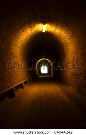 tunnel illuminated with light at the end - stock photo