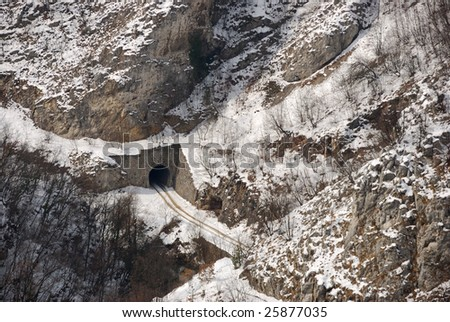 Tunnel in a hill and car trails in snow