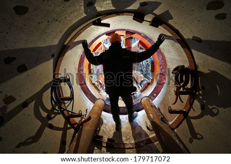 Tunneller sinker worker connecting equipment in tunnel - stock photo
