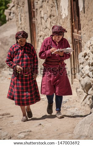 TUPE, LIMA, PERU - FEBRUARY 3: Instant of a women in traditional clothing, while walk though town on February 03, 2010 in Tupe, Peru. In the Andes, people walk a lot on difficult  trails.  - stock photo