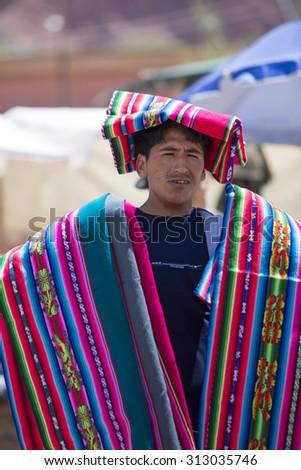 TUPIZA, BOLIVIA, DECEMBER 28: Vendor carrying traditional Bolivian fabrics, rugs and souvenirs during the Saturday town market of Tupiza, Bolivia 2014. - stock photo