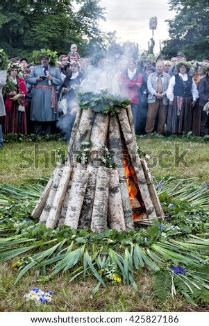 TURAIDA, LATVIA - JUNE 21, 2011: Crowd of people around bonfire celebrating Midsummer summer solstice - Jani. It is a traditional pagan festivity marking the shortest night of the year. - stock photo