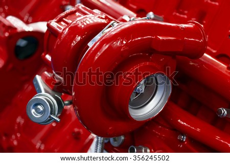 Turbocharger of red powerful engine, turbine of diesel motor for oversize trucks, SUV, cargo, commercial and construction vehicles, heavy industry, detail