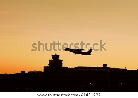 Turboprop plane flying over the airport tower in sunrise - stock photo