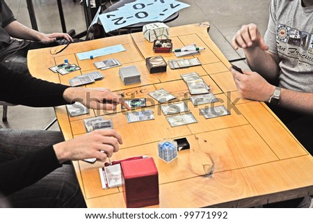 TURIN - APRIL 1: A match with the fantasy card game of Magic The Gathering on a wooden table during the tournament Grand Prix Turin on April 1, 2012 Turin, Italy. - stock photo