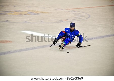 "TURIN - FEBRUARY 25: Unidentified Italian player controls puck during qualification's match Italy Vs Czech Republic. Ice Sledge Hockey tournament ""Città di Torino"" on February 25, 2012 Turin, Italy. - stock photo"