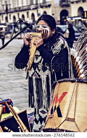 Turin, Italy - April 27, 2013: Red indian in traditional costume plays in the center of Turin, Italy. Street performance of a group of Native Americans with sounds and traditional dancing. - stock photo