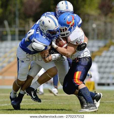 TURIN, ITALY - APRIL 12, 2015: Unknown american football players fight during match. Italian U19 team win the qualifying match with Spain for European championship, in the Nebiolo Stadium in Turin.
