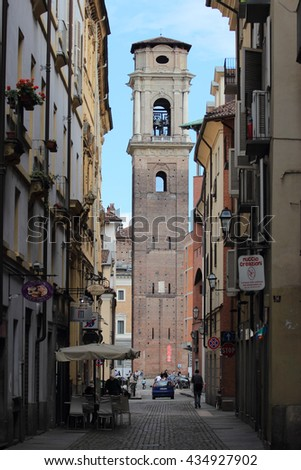 TURIN, ITALY - JUNE 5, 2016: local life with a sight of the bell tower of Saint John the Baptist Cathedral