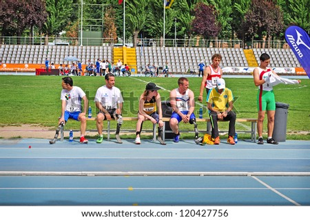 TURIN - MAY 12: Unidentified athletes relaxing on a bench during the Italian Championships of Athletics for paralympic athletes on May 12, 2012 Turin, Italy. - stock photo