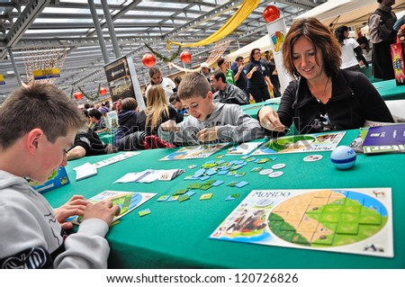 TURIN - NOVEMBER 25: An unidentified family plays a boardgame during the exhibition of games at the gathering GiocaTorino in Lingotto, on November 25, 2012 Turin, Italy. - stock photo