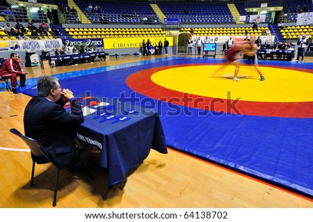 TURIN - OCT 29: Judge looking at fighting wrestlers in the fight arena during Wrestling 2010 9th World University Championship, October 29, 2010 in Turin, Italy.