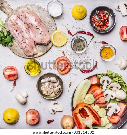 Turkey breast On a cutting board with herbs different fruits and vegetables Cucumbers mushrooms tomato salad pepper and lemon in a frying pan on rustic wooden background top view close up - stock photo
