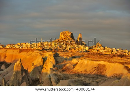 Turkey. Cappadocia. View on rock-castle of Uchisar town across a Guyercinlik valley at a sunrise