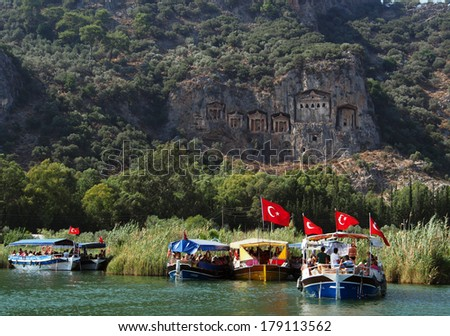 TURKEY, DALYAN, MUGLA - JULY 19, 2013: Pleasure boat with tourists in the mouth of the Dalyan River under Lycian tombs - stock photo