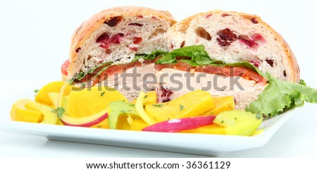 Turkey, mayo, lettuce, tomato on cranberry roll.  On plate with yellow beet salad on side. - stock photo