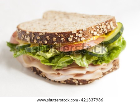 turkey sandwich with vegetables, bread with cereals, close up shot with selective focus on white background - stock photo