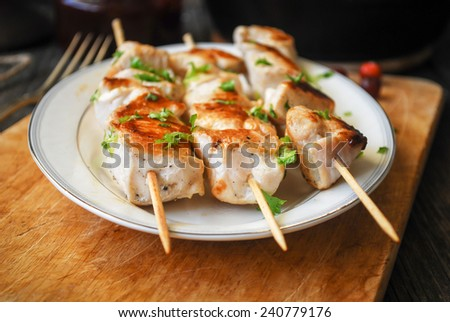 Turkey skewers garnished with parsley on white plate - stock photo