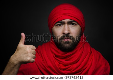 Turkish and Arabic theme: beautiful Arabic man with a beard in a red scarf showing gestures isolated on black background in studio - stock photo