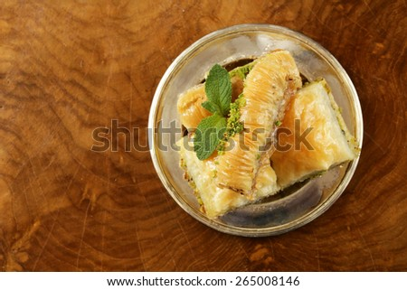 Turkish arabic dessert - baklava with honey and walnut, pistachios nuts on wooden background top view - stock photo