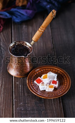 Turkish coffee and Turkish Delight over dark wooden background. Selective focus, Shallow DoF, dramatic lighting, vintage - stock photo