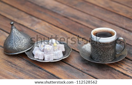 Turkish coffee and turkish delight with  old traditional embossed  metal cup - stock photo