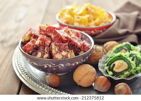 Turkish delight with nuts and sesame in ceramic bowl on wooden background