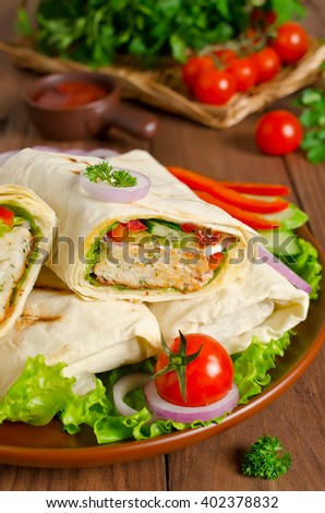 Turkish doner kebab, shawarma, roll with meat, vegetables and pita bread on a wooden background