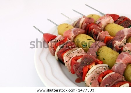 Turkish kebabs with beef, lamb, pork, onion, red and green peppers, with spicy herb potatoes on skewers, on white, copy space, macro, close up - stock photo