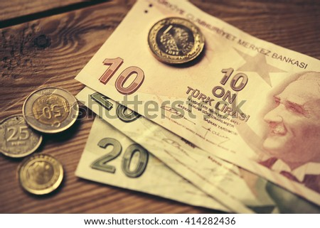 Turkish lira bills and coins on wooden table. Toned image - stock photo