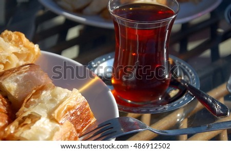 Turkish meat pie fried in oil (borek )  and  traditional turkish tulip glass of tea
