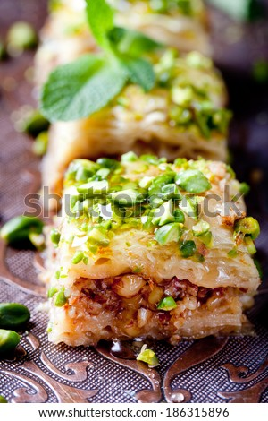 Turkish pistachio and phyllo pastry dessert, baklava on a authentic cooper tray with a plate of pistachios and stick of cinnamon  - stock photo