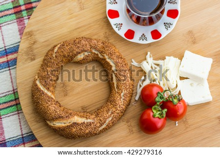 turkish simit, tea, cherry tomato and cheese  on a circle wooden surface on a red and blue plaid tablecloth at home in the kitchen balcony - stock photo