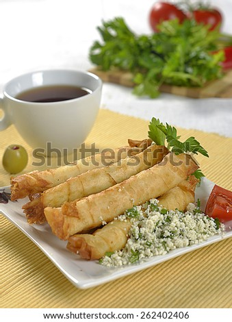 Turkish style cheese stuffed filo dough rolls served along on lettuce leaves along with tomatoes - stock photo