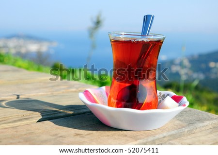 turkish tea on a table on nature with sea view - stock photo