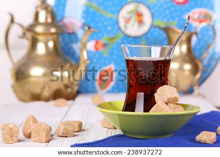 Turkish tea with cane sugar  on a white table - stock photo