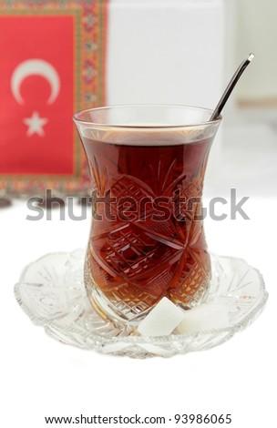 Turkish tea with traditional crystal tea glass and turkish flag - stock photo