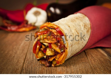 Turkish traditional doner with vegetables cheddar cheese wrap on wooden background - stock photo