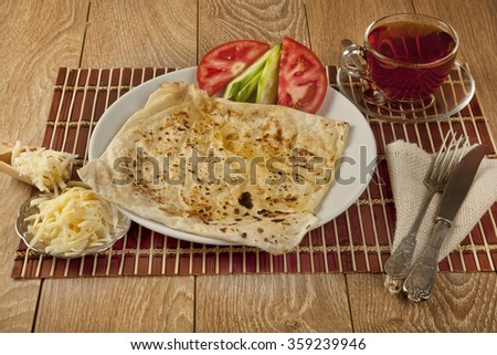Turkish traditional Gozleme pita cheddar cheese with black tea - stock photo